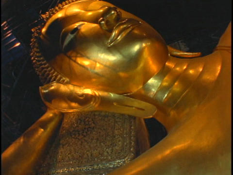 A golden Buddha statue sits in a temple in Bangkok, Thailand Footage