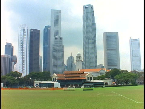 The skyline of Singapore rises above an upper class cricket club Footage