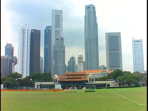 The skyline of Singapore rises above an upper class cricket club Live Action