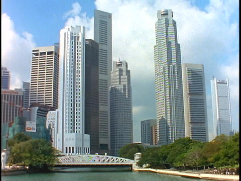 The skyline of Singapore rises above a bridge spanning a river Footage