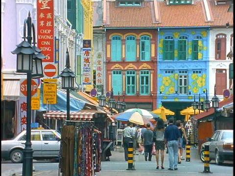 Pedestrians and shoppers walk down a colorful street in Asia Footage