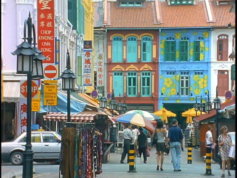 Pedestrians and shoppers walk down a colorful street in Asia Stock Video Footage