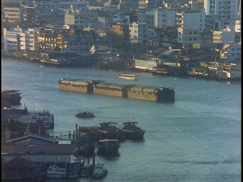 A shipping barge moves along the Chao Praya River in Bangkok, Thailand Footage