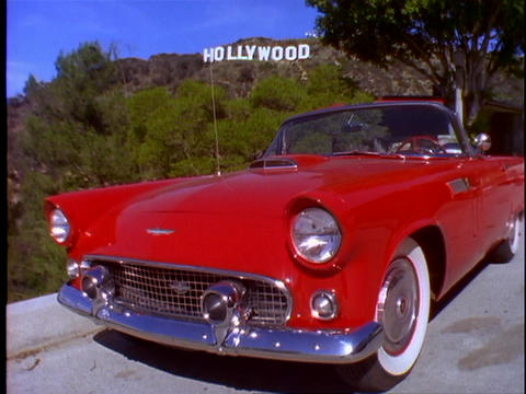 A classic Ford Thunderbird car is parked on a street below the Hollywood Sign in Los Angeles, Califo Footage