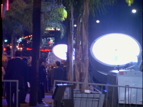 Searchlights light up the night sky in Hollywood, CA announcing a big movie premiere Footage