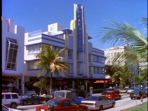 Pedestrians and car traffic pass by an art-deco building in Miami Beach, Florida Footage