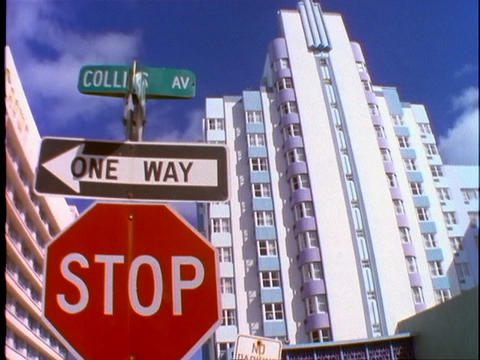A stop sign, one way sign and a street sign stands in front of an art deco apartment building in Mia Footage