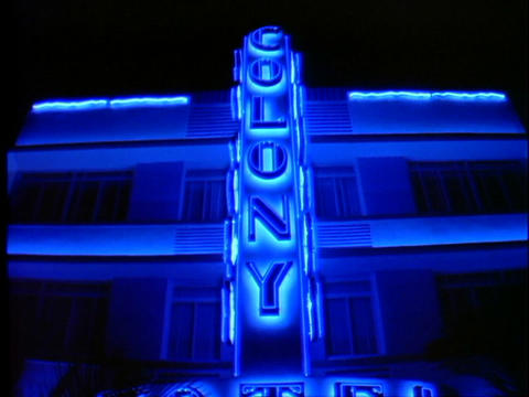 The neon sign for the art-deco Colony hotel is lit up at night Footage