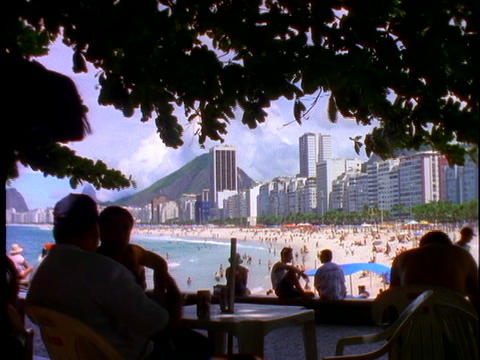 Silhouetted people sit at tables in an outdoor cafe with... Stock Video Footage