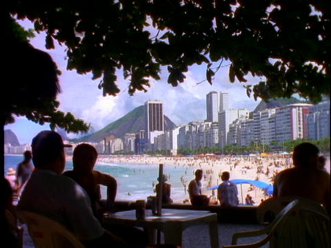 Silhouetted people sit at tables in an outdoor cafe with Copacabana beach in the background Footage