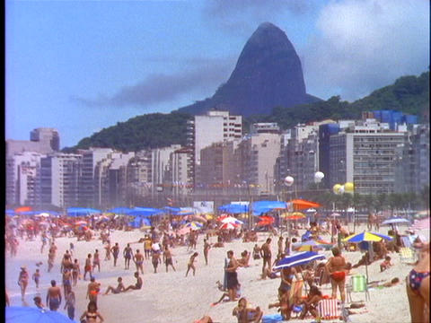 Sunbathers lie in the sand on Copacabana beach in Rio De Janeiro with Corcovado mountain in the back Footage