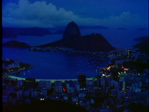 Corcovado mountain is silhouetted against the ocean overlooking Rio De Janeiro, Brazil Footage