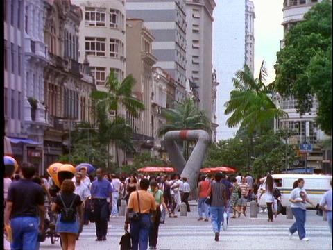 Shoppers and pedestrians walk through a shopping district... Stock Video Footage
