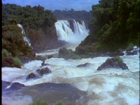 The Iguacu Falls fall into a flowing river Live Action
