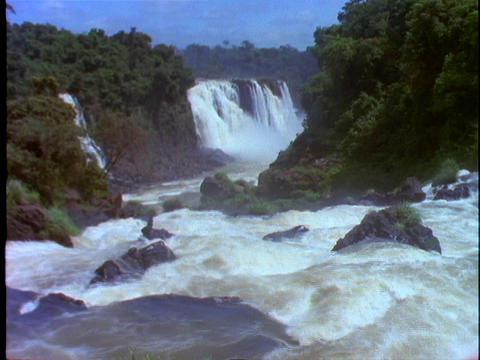 The Iguacu Falls fall into a flowing river Stock Video Footage