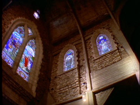 Stained glass windows adorn the interior of a Catholic... Stock Video Footage