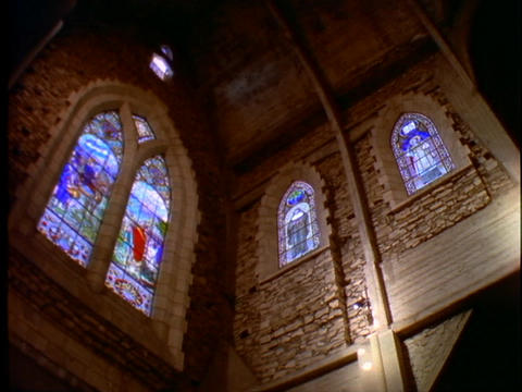 Stained glass windows adorn the interior of a Catholic church Footage