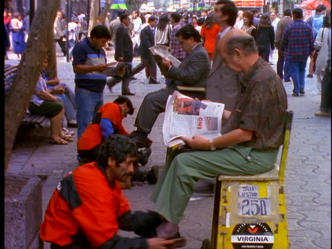 Shoe shiners polish shoes on a busy main street in Lima, Peru Footage