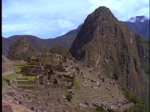 The ruins of Machu Picchu nestle at the top of the mountains in Peru Footage