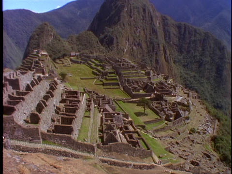 The ruins of Machu Picchu nestle at the top of mountains... Stock Video Footage