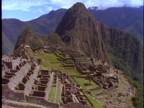 The ruins of Machu Picchu nestle at the top of mountains in Peru Footage