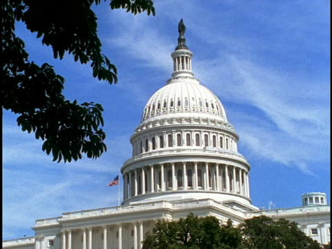 A flag waves from the roof of the U.S. Capitol building Footage