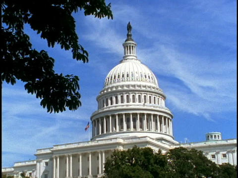 A flag waves from the roof of the U.S. Capitol building Stock Video Footage