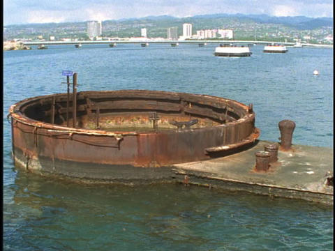 The top of a large rusty tank sits open above the oceans surface at the USS Arizona Memorial in Pear Footage