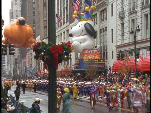 Snoopy and Garfield balloons float in the Macys Thanksgiving Day Parade Footage