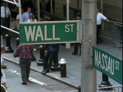 Crowds of people walk on the corner below the street signs of Wall and Nassau street in New York Cit Footage