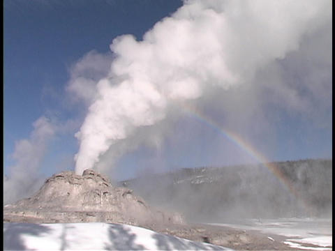 A rainbow forms behind the Castle Geyser in Yellowstone National Park Footage