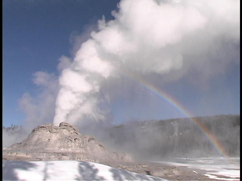 A rainbow forms behind the Castle Geyser in Yellowstone... Stock Video Footage