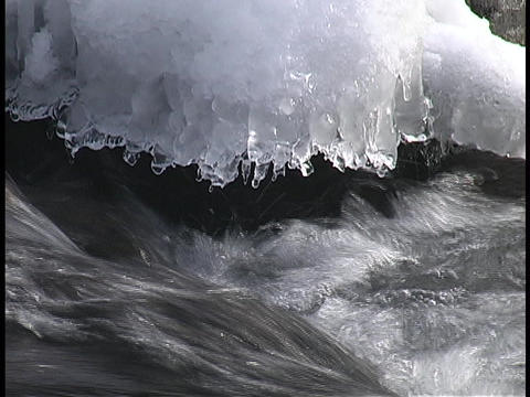 Ice and snow melt into a river Stock Video Footage