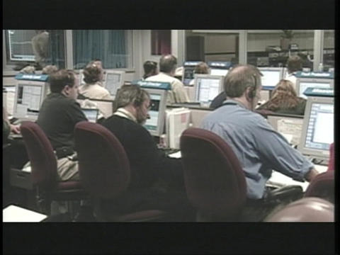 Technicians work at computers in the NASA control room Stock Video Footage