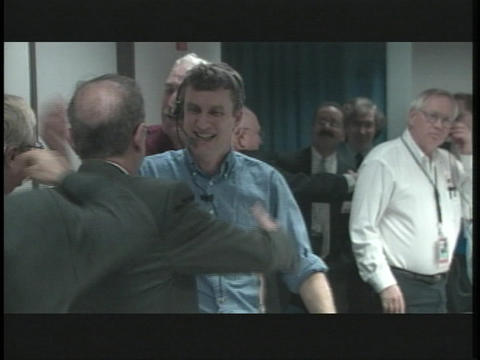 Scientists celebrate in the control room at NASA Footage