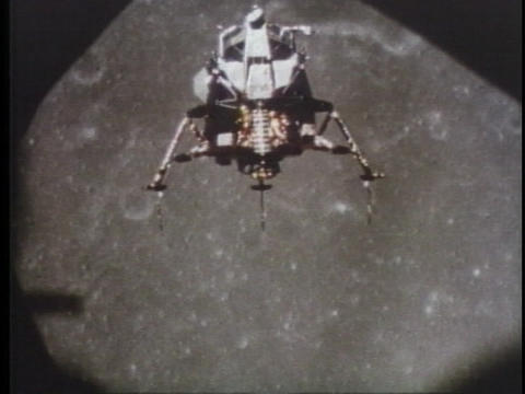 The NASA moon lander floats over the moon Live Action