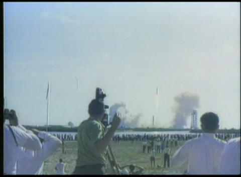 Distant shot of a rocket launch by NASA with cameramen in foreground Footage