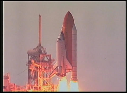 Pan of space Shuttle lifting off from launch pad Footage