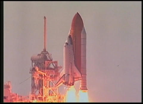 Pan of space Shuttle lifting off from launch pad Stock Video Footage