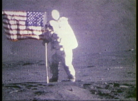 Long-shot of an astronaut placing the American Flag on the moon Footage