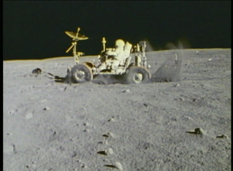 Hand-held shot of astronauts driving a lunar vehicle on the moon Footage