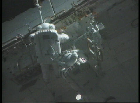 Medium shot of astronauts fixing panels on the International Space Station Live Action