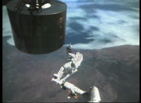 Hand-held shot of an astronaut repairing a satellite... Stock Video Footage