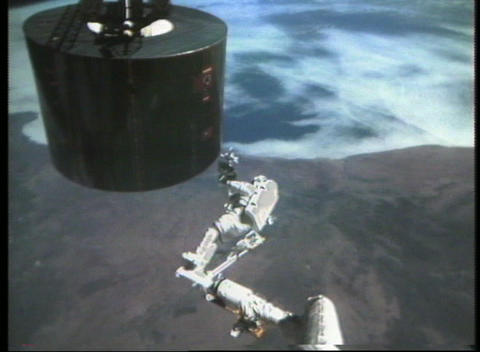 Hand-held shot of an astronaut repairing a satellite while in orbit above the Earth Footage