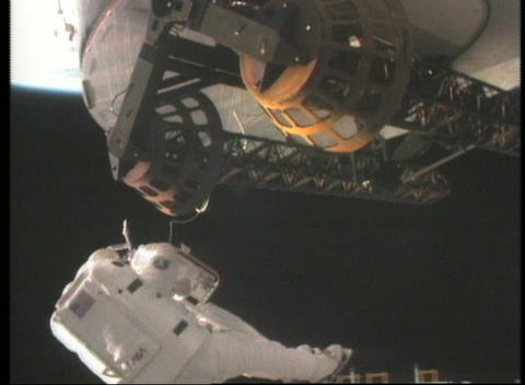 Medium shot of an astronaut repairing a satellite in space Footage
