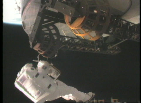 Medium shot of an astronaut repairing a satellite in space Stock Video Footage