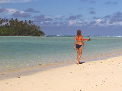 A vacationer strolls across a tropical beach Stock Video Footage