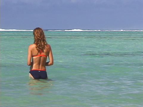 A vacationer stands in the ocean Footage