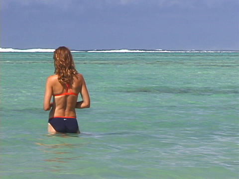 A vacationer stands in the ocean Stock Video Footage