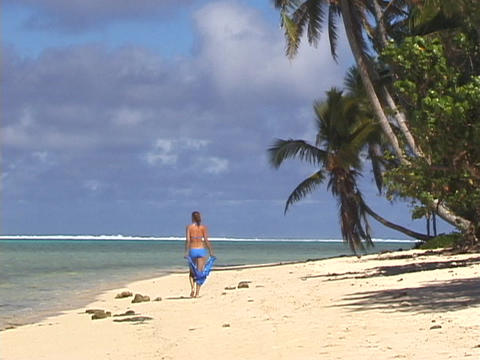 A vacationer strolls down a tropical beach Stock Video Footage